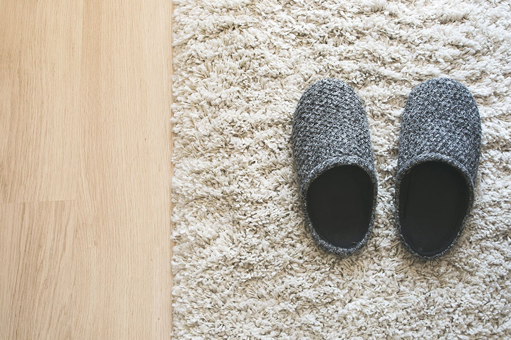 gray slippers on the carpet How to save material when renovating your old house